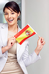 Attractive happy young woman holding a Spanish flag