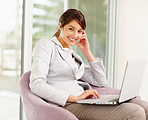 Cute young business woman using a laptop