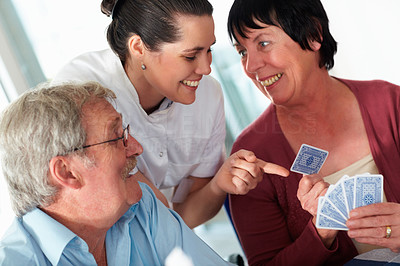 Young nurse assisting an elderly woman in a game of cards