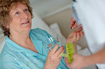 Senior woman being given a pill by doctor