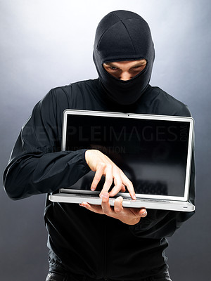 Buy stock photo Portrait of a young male thief stealing informatin from laptop