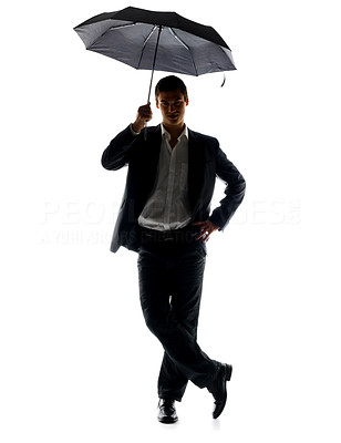 Buy stock photo Portrait of a handsome young business man standing under umbrella against white background