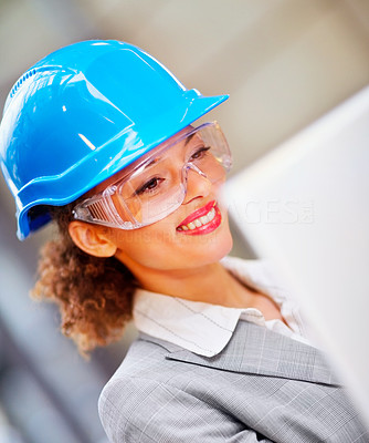 Happy young female architect with a hard hat and safety glasses