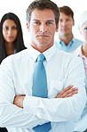 Confident young businessman standing in front of his team