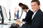 Smiling young businessman working on computer