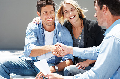 Young couple shaking hand with insurance advisor