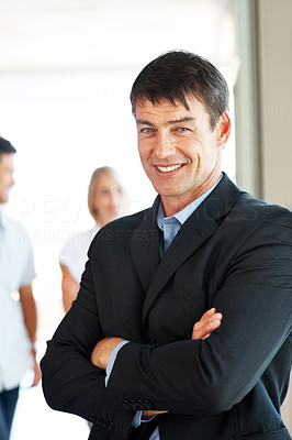 Confident businessman standing with arms crossed