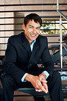 Successful businessman sitting on steps and smiling