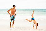 Happy man watching his son doing a cartwheel on the beach