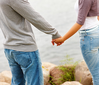 Mid section of a young couple holding hand outdoors