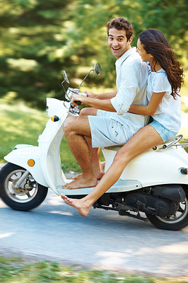 Buy stock photo Full length shot of a young couple riding their scooter in the park