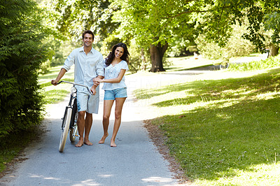 Buy stock photo Full length shot of an affectionate young couple cycling in the park