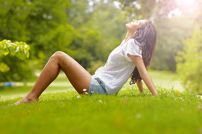 Buy stock photo Full length shot of a young woman sitting in the park
