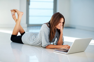 Buy stock photo Pretty young woman lying on floor working on lapto