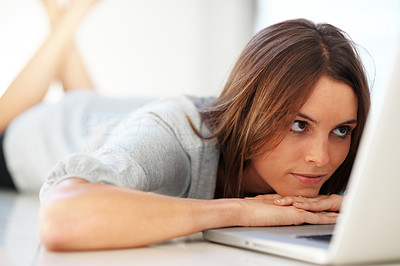 Buy stock photo An attractive young woman lying on floor looking a