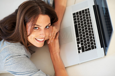 Buy stock photo Beautiful young woman lying on floor with a laptop