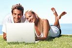 Lovely couple using laptop in park