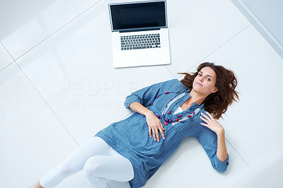 Buy stock photo Young woman relaxing on the floor with laptop