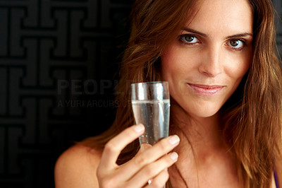 Buy stock photo Closeup portrait of an attractive young woman smiling at the camera while holding up a glass of champagne