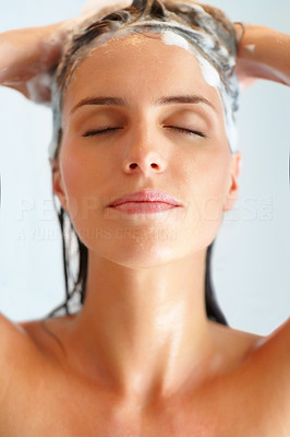 Buy stock photo Cute young woman washing her hair with shampoo