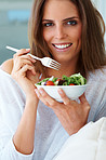 Charming young woman eating green salad