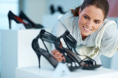 Buy stock photo Beautiful young woman choosing shoes at a store