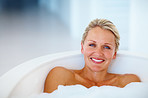 Cute mature woman relaxing in the bathtub