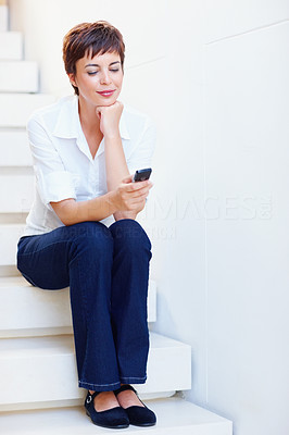 Happy female on the stairs text messaging