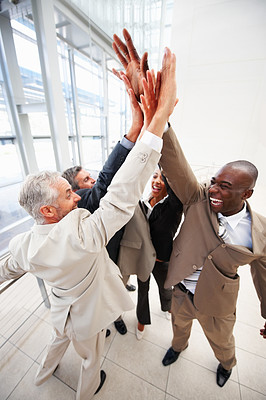 Successful business team with their hands raised together in agreement
