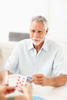 An old man playing a game of cards, smiling