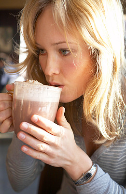 Buy stock photo Pretty young woman blowing on her delicious hot cacao