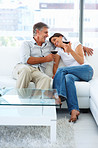Charming mature couple sitting on a couch and drinking a glass of wine