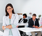 Happy business woman with her hands folded with colleagues working at the back
