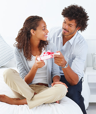 Portrait of a young romantic husband giving a gift to his lovely wife sitting on the bed