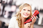 Happy young woman holding a red shoe at a store