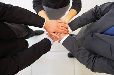 Buy stock photo High angle shot of a group of corporate businesspeople with their hands together in a huddle