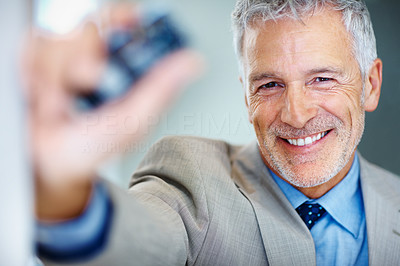 Buy stock photo Shot of a businessman showing you his cellphone