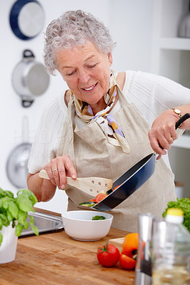 Old woman holding a pan and preparing food in kitchen