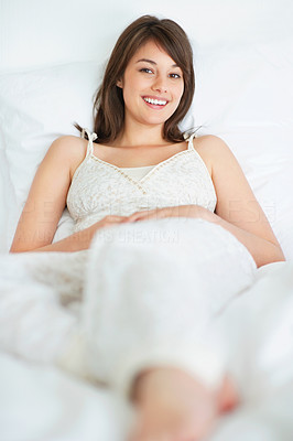 Buy stock photo Happy young woman relaxing in bed