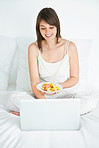 Young woman using laptop while eating fruit salad