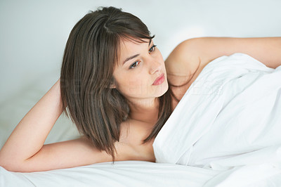 Buy stock photo Thoughtful young female lying on the bed