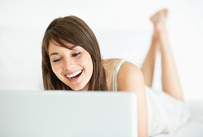 Buy stock photo Cheerful young lady lying and using a laptop