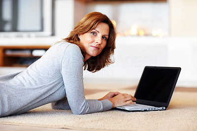 Buy stock photo Pretty young woman using laptop while lying on flo