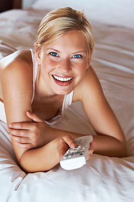 Attractive woman enjoying a TV show in bed