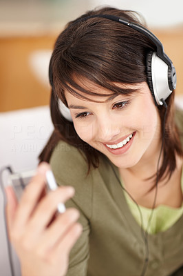 Buy stock photo Cute young female hearing music from an mp3 player