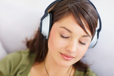 Buy stock photo Closeup of a pretty girl listening to pleasant music on her headphones