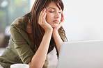 Stressed young female using a laptop at home
