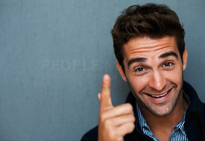 Buy stock photo Studio portrait of a confident young man pointing and smiling