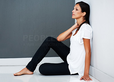 Buy stock photo Pretty woman sitting against the wall