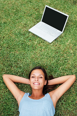 Buy stock photo Pretty woman laying on the grass near laptop